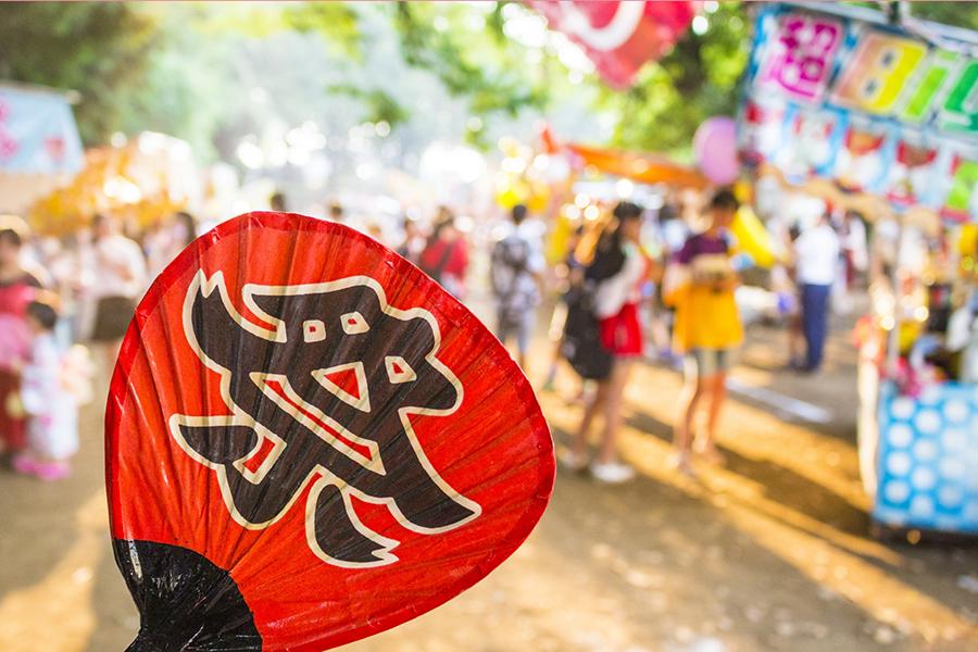 赤いうちわに「祭」と書かれた夏祭りのイメージ写真