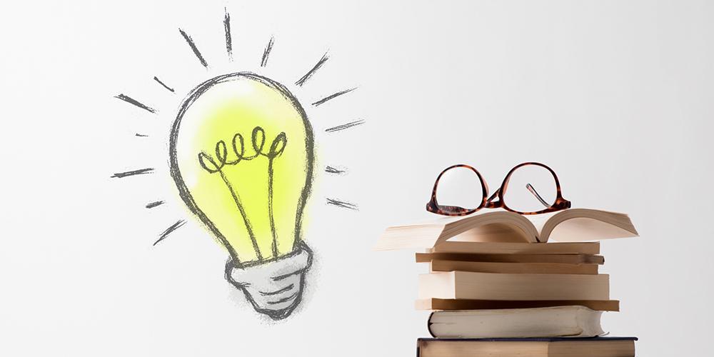 積み重ねた本と電球のイラスト