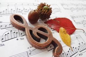 楽譜の上に置かれた落ち葉と栗とト音記号