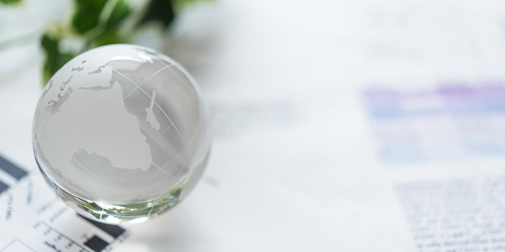 書類の上に乗ったガラスの地球儀