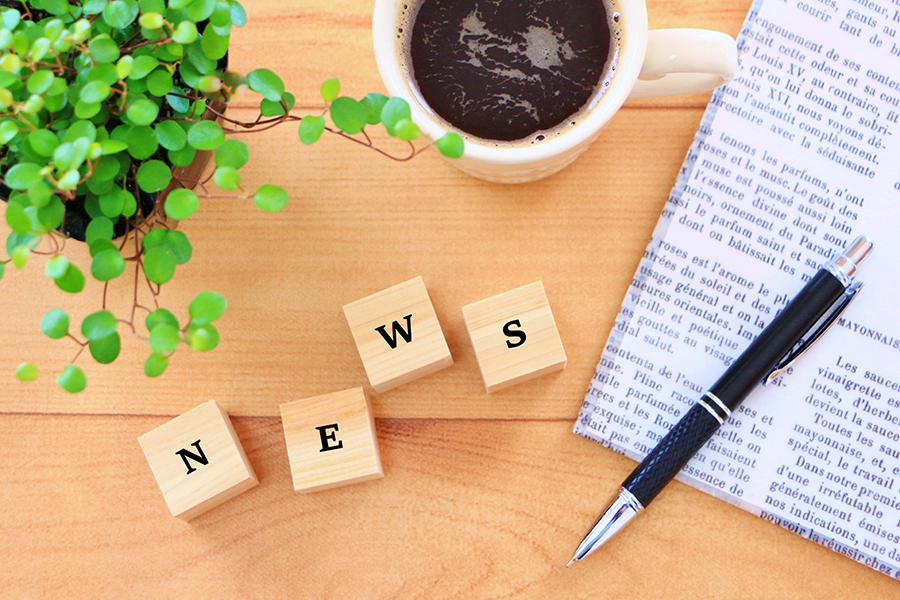 机の上に置かれたコーヒーとペンと新聞と「NEWS」の文字