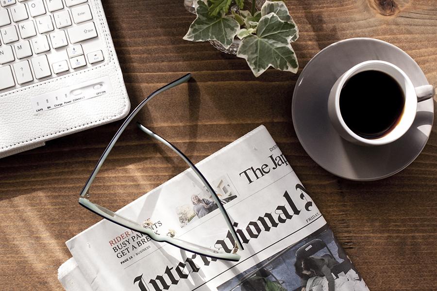 木のテーブルに乗ったパソコンとコーヒーと新聞の写真